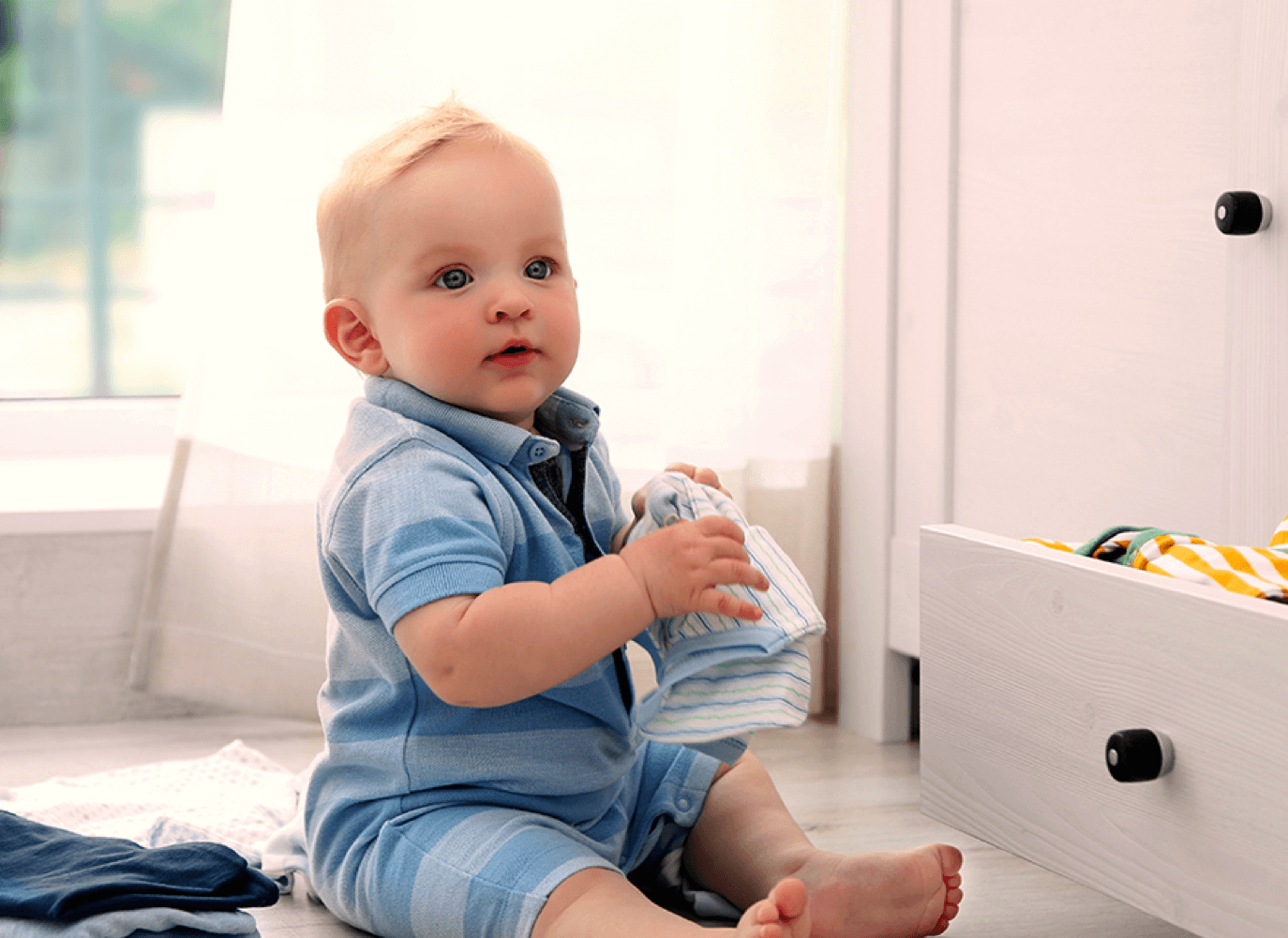 A baby sits on the floor and plays with some laundry. He is looking off camera