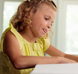 A young female child named Quinn concentrates intently on her homework while sitting at a table